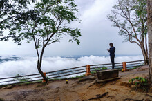 Tourists Taking Pictures Of The Scenery At The Viewpoint Of The Cliff That Has Fog Around The Mountain. Pha Mo E Dang, Thailand