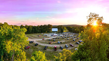 Outdoor Drive-In Movie Theater With Pink Sunset. Aerial Drone View Looking Over Cars From Back Of Parking Lot Towards White Movie Screen.