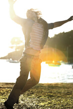 Young Man Jumping On A Pebbly Beach, Arms Raised, Moored Sailing Boats In The Background, Sunlight.