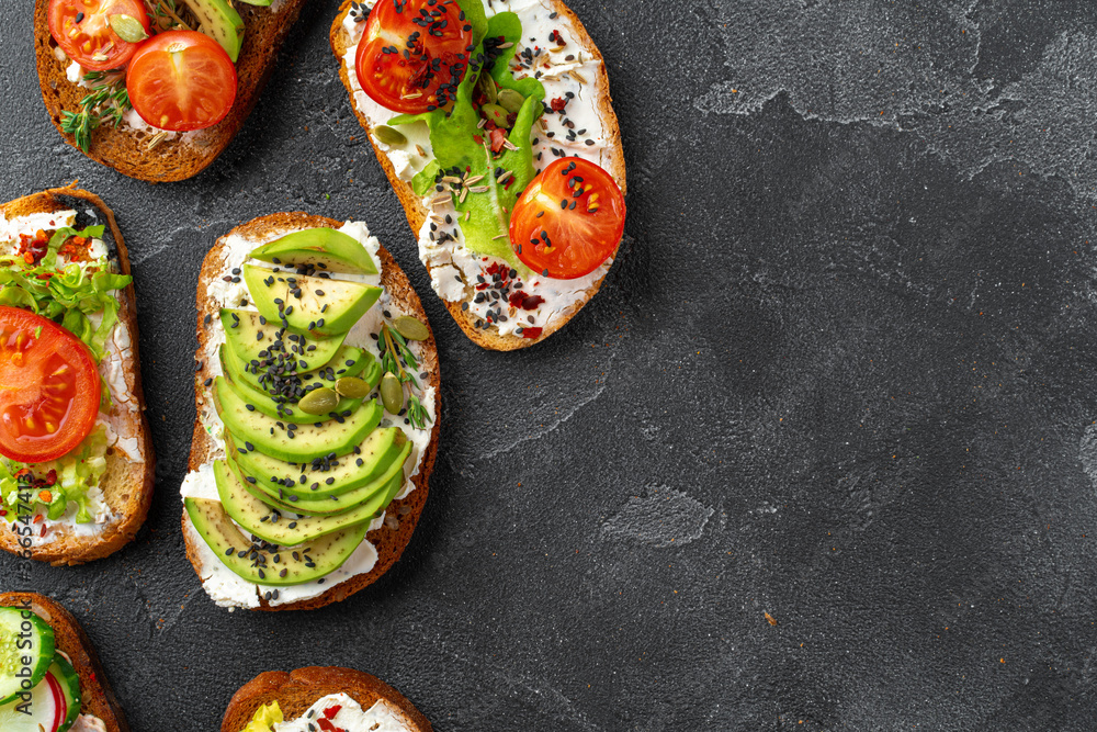 Fototapeta Assortment of vegan sandwiches with avocado and tomatoes