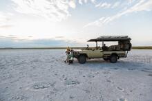 A Safari Vehicle Parked In The Salt Pans Landscape At Dusk.