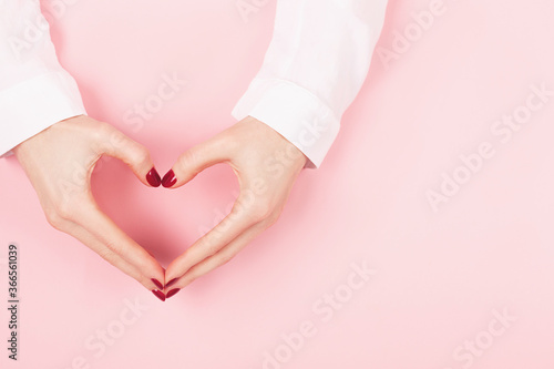 Woman hands with perfect manicure in a heart shape on pink background Canvas Print