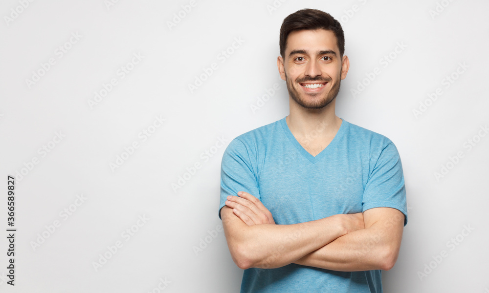 Fototapeta Banner of young handsome man wearing blue t-shirt, standing with crossed arms, isolated on studio gray background
