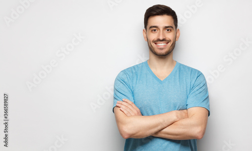 Obraz Banner of young handsome man wearing blue t-shirt, standing with crossed arms, isolated on studio gray background - fototapety do salonu