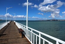 Wooden Pier With White Railing, Blue Sea And Blue Sky