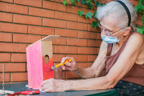Valokuva old woman with face mask painting a birdhouse