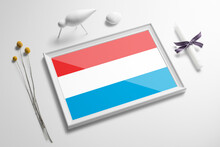 Luxembourg Flag In Wooden Frame On Table. White Natural Soft Concept, National Celebration Theme.