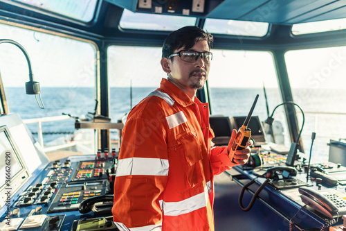 Obraz Filipino deck Officer on bridge of vessel or ship wearing coverall during navigaton watch at sea . He is speaking on portable GMDSS VHF radio, short range communication - fototapety do salonu