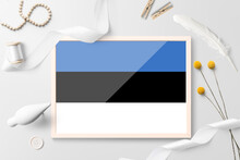 Estonia Flag In Wooden Frame On White Creative Background. White Theme, Feather, Daisy, Button, Ribbon Objects.