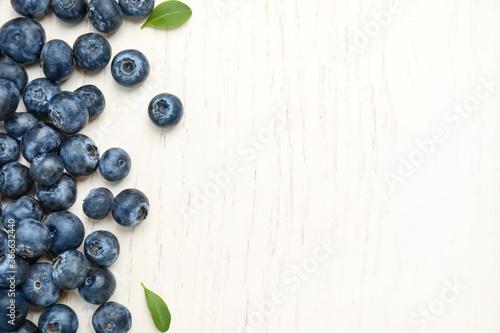 Cuadros en Lienzo Fresh ripe blueberries on white wooden table, flat lay
