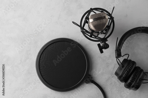 Studio microphone with professional headphones on a light background, top view Fototapeta