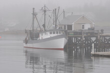 Calm, Restful Scene In Coastal Maine. Fishing Trawler Anchored Alongside Dock And Enveloped In Thick Fog At Picturesque Fishing Village Of Port Clyde.