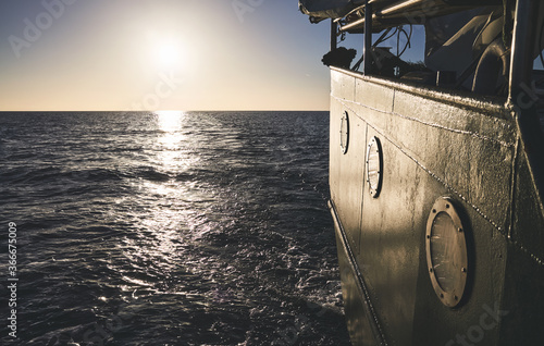 Fotografie, Obraz Stern of an old ship at sunset, travel or homesickness concept.