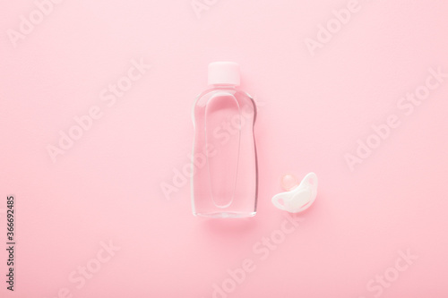 Fotografie, Obraz Transparent plastic bottle of oil and white soother for baby on light pink table background