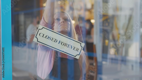 Fototapeta Senior woman business owner bankrupt hanging up sign with inscription closed forever obraz
