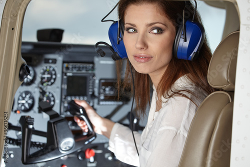 Young Woman Pilot With Headset Looking Through The Cockpit Window Fototapete