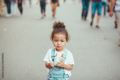 Photo Cute little girl eating ice-cream in the street