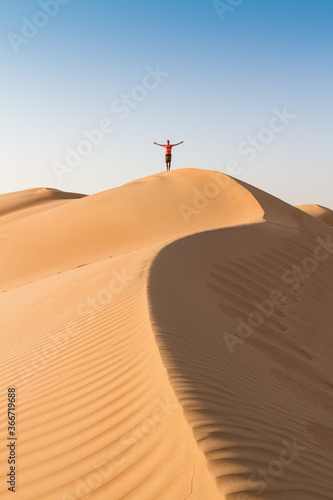 Fototapeta Male traveler standing on the top of dune, arms up to the sky, while traveling sand dessert in Oman. Travel adventure concept. obraz