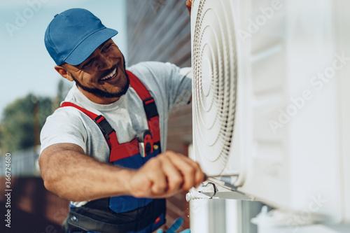 Fototapeta Young black man repairman checking an outside air conditioner unit