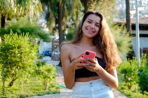 Fotografering Portrait of young beautiful woman with long wavy brunette hair with her phone in tropical destination park with greenery on the background