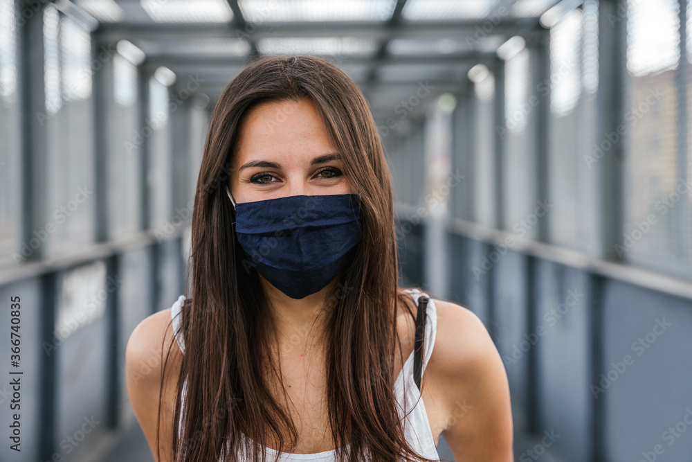 Fototapeta Portrait of beautiful woman on iron bridge in the summer in the city with face mask for protection from contagion by Coronavirus, Covid-19 - Millennial looking and smiling - Concept of naturalness