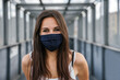 Portrait of beautiful woman on iron bridge in the summer in the city with face mask for protection from contagion by Coronavirus, Covid-19 - Millennial looking and smiling - Concept of naturalness