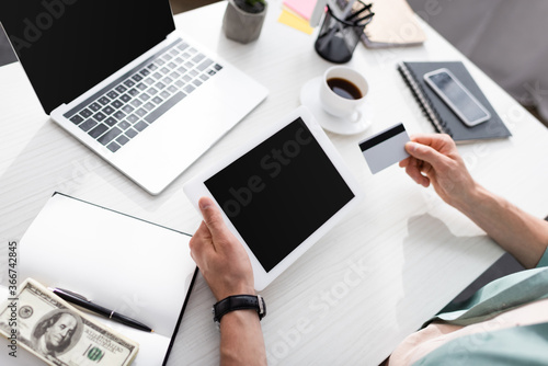 Obraz Cropped view of man holding credit card and digital tablet with blank screen near dollars and notebook on table, earning online concept - fototapety do salonu