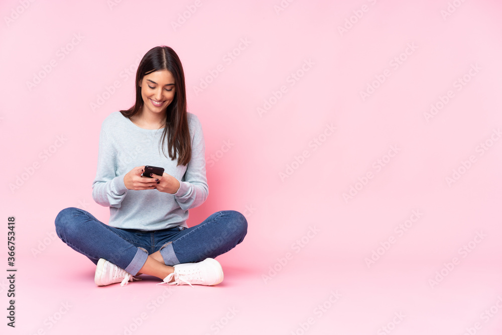 Fototapeta Young caucasian woman isolated on pink background sending a message with the mobile