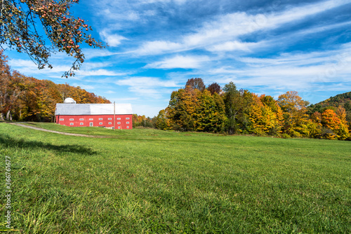 Traditional red barn at the far end of a grassy field with deciduous trees in background on a clear autumn day Wallpaper Mural