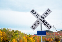 Railroad Crossing Sign In The Countryside On A Cloudy Autumn Day. Colouful Autumn Trees Are Visible In Background. Copy Space.