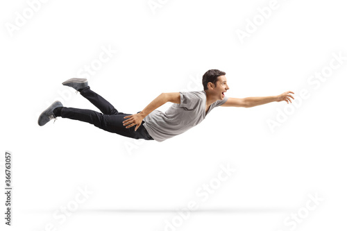 Photographie Casual young man flying and reaching for something