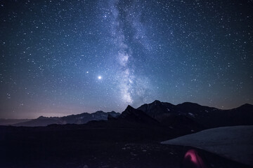 Milky way galaxy stars in the night sky over the Alps, illuminated camping tent in foreground,  snowcapped mountain range, astro photography stargazing