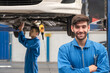 Confident Caucasian expert mechanic standing with his arms crossed and holding wrench at work shop car garage and smiling at camera while another one working on the background.