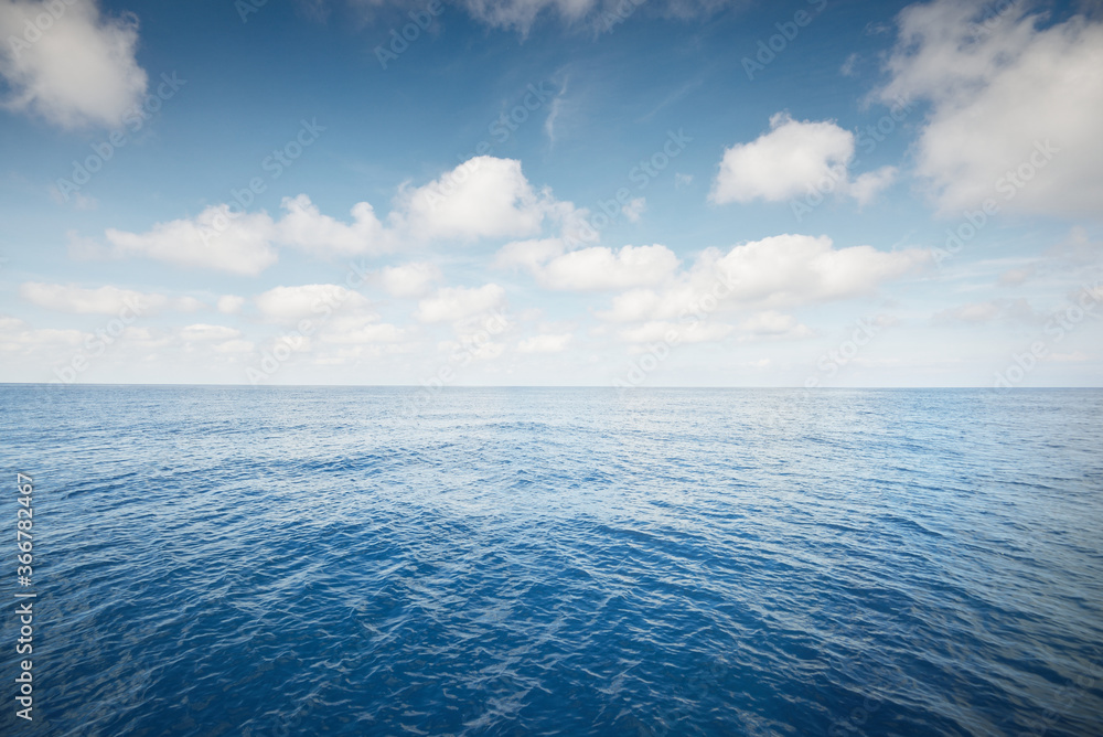 Fototapeta Clear blue sky with cumulus clouds above the Mediterranean sea. Idyllic seascape. Travel destinations, sport, sailing, cruise, recreation, vacations, environmental conservation concepts