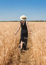 A Girl In A Hat In A Wheat Field