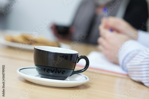 Fotografia Black cup with white saucer on a large desk with a mans arm in a blue shirt in t