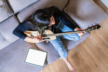 Woman Playing Guitar Sitting O...