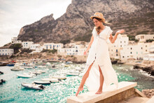 Smiling Female Tourist In Summer Wear Standing Barefoot On Stone Fence During Vacation On Background Of Harbor With Boats And Looking Down