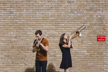 Creative Boyfriend And Girlfriend In Summer Outfit Standing On Background Of Old Brick Wall And Playing Brass Musical Instruments While Entertaining During Weekend In City