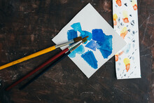 Top View Of Watercolor Samples And Paintbrushes Placed On Wooden Table Near Aquarelle Palette And Blank Sheet Of Paper