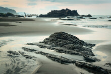 Sea Waves Rolling On Wet Sandy Seashore With Rough Rocky Formations And Distant Silhouette Of Female Traveler In Summer Evening In Taiwan