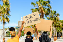 Back View Of Ethnic Female With Afro Hairstyle Holding Cardboard Poster With Black Lives Matter Inscription During Demonstration At Beach