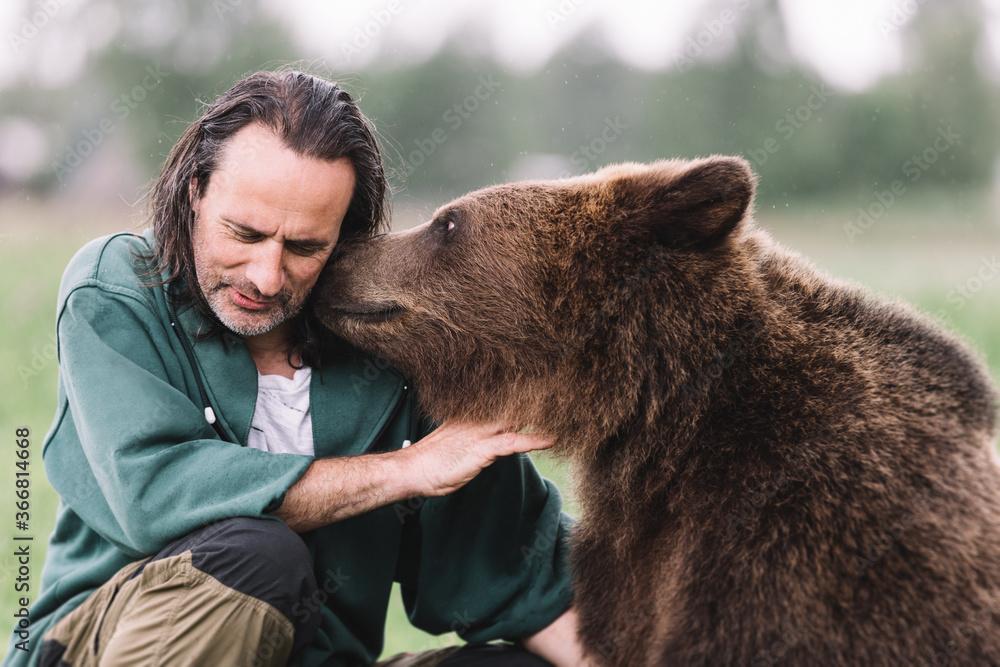 Fototapeta An adult man and a bear hug.