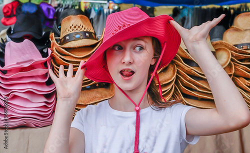 Fotografie, Obraz Funny portrait of a young girl in a pink cowboy hat  - goofy look on face with t