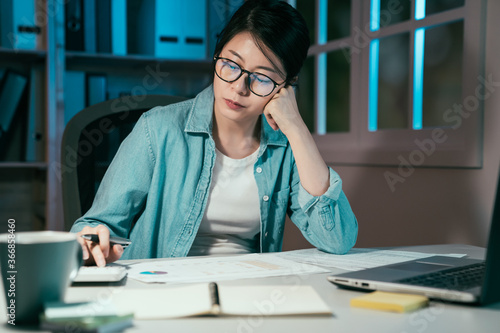 Close up of woman freelance worker using calculator while going through company finances in dark night Fototapeta