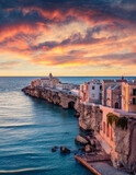 Stunning morning cityscape of Vieste - coastal town in Gargano National Park, Italy, Europe. Colorful summer sunrise on Adriatic sea. Traveling concept background.