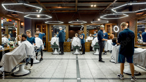 People at barbershop. Professional barbers serving clients in the modern loft style barber shop. General view. Hairdresser services
