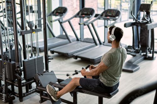 Photo Young sportsman having cross training on rowing machine at health club