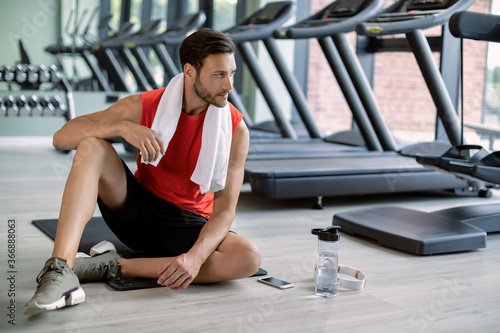 Young sportsman relaxing on exercise mat in health club. Fotobehang