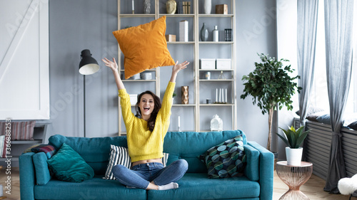Foto Joyful woman in a yellow sweater and jeans sitting on a cozy sofa throw a pillow up in the living room at home